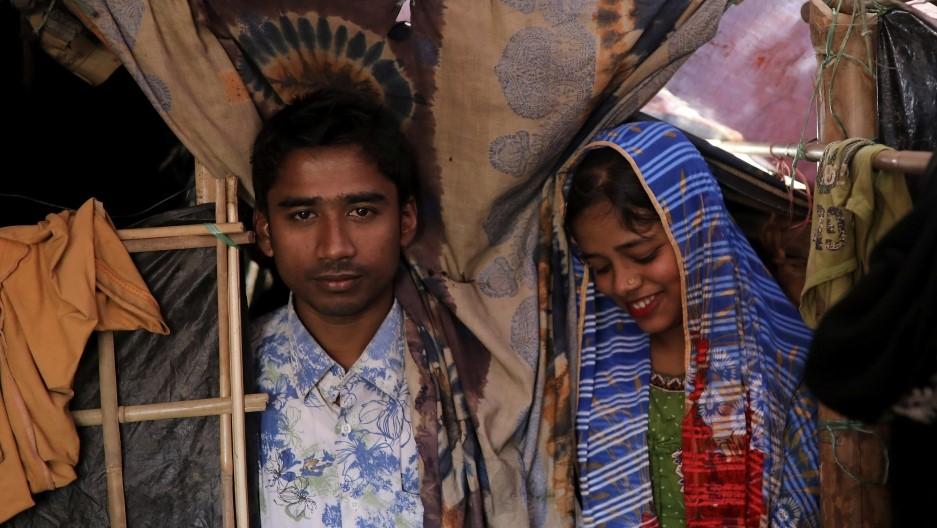 Беженцы-рохинья 23-летний Саддам Хуссейн и его 18-летняя жена Шофика Бегум в своем временном убежище в лагере беженцев «Кутупалонг» около города Кокс-Базар (Бангладеш). Руки невесты покрыты декоративными узорами, украшенными хной, жених умащен благовониями, а гости пируют и танцуют всю ночь в красочной палатке. Источник фото: Marko Djurica/Reuters